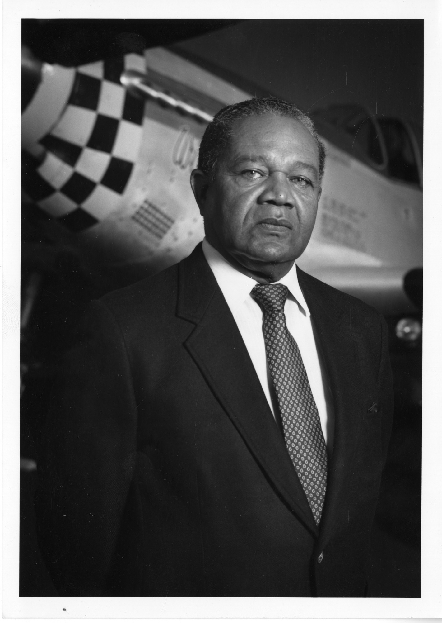 Louis R. Purnell, Jr., Curator of Astronautics, in Front of Airplane at NASM