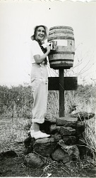 "Female expedition member at Charles Island barrell ""post office."""
