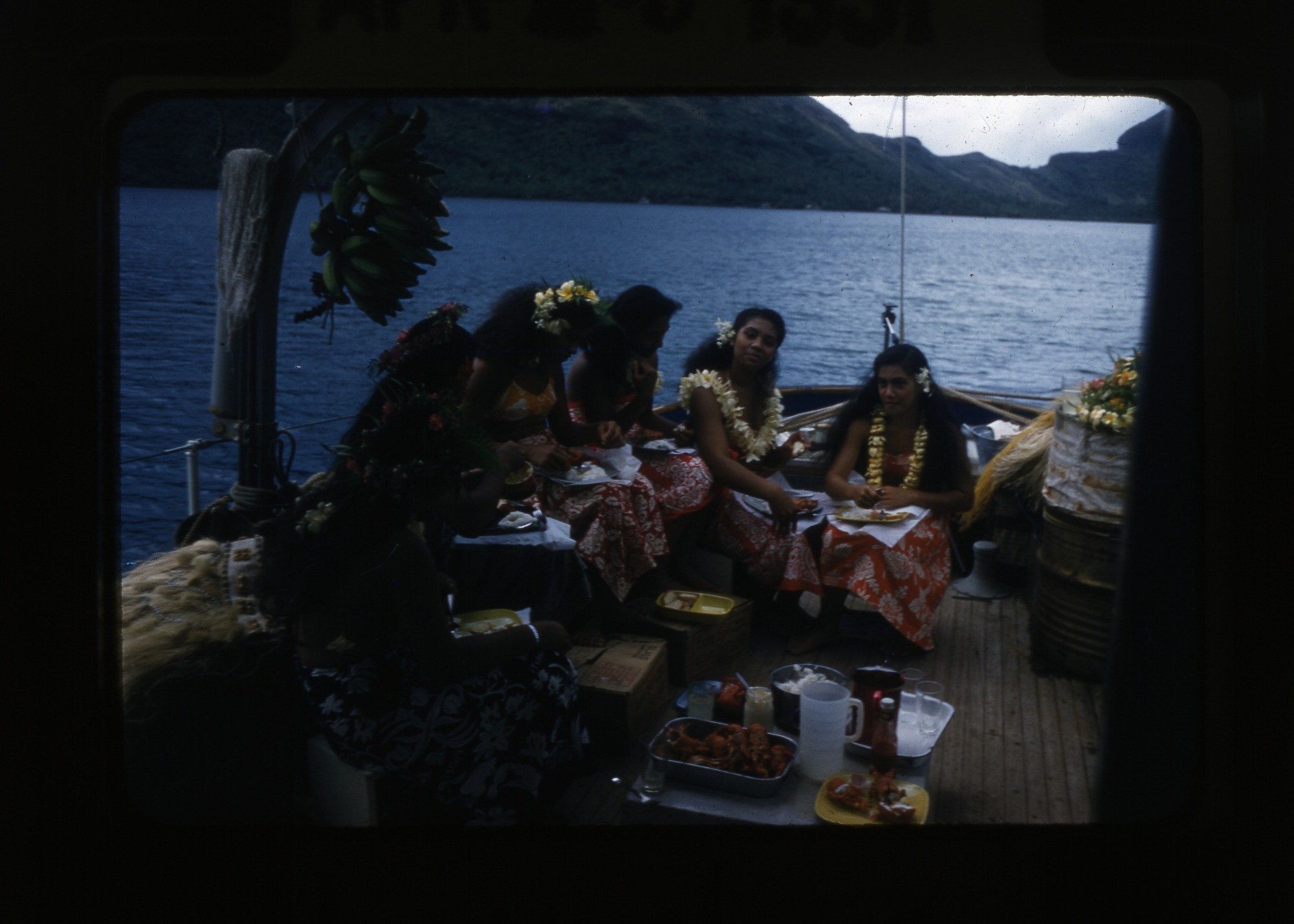 Lunch aboard the vessel Mureva, with dancers from Bora Bora (in local dance competition) consuming lobster, 1957