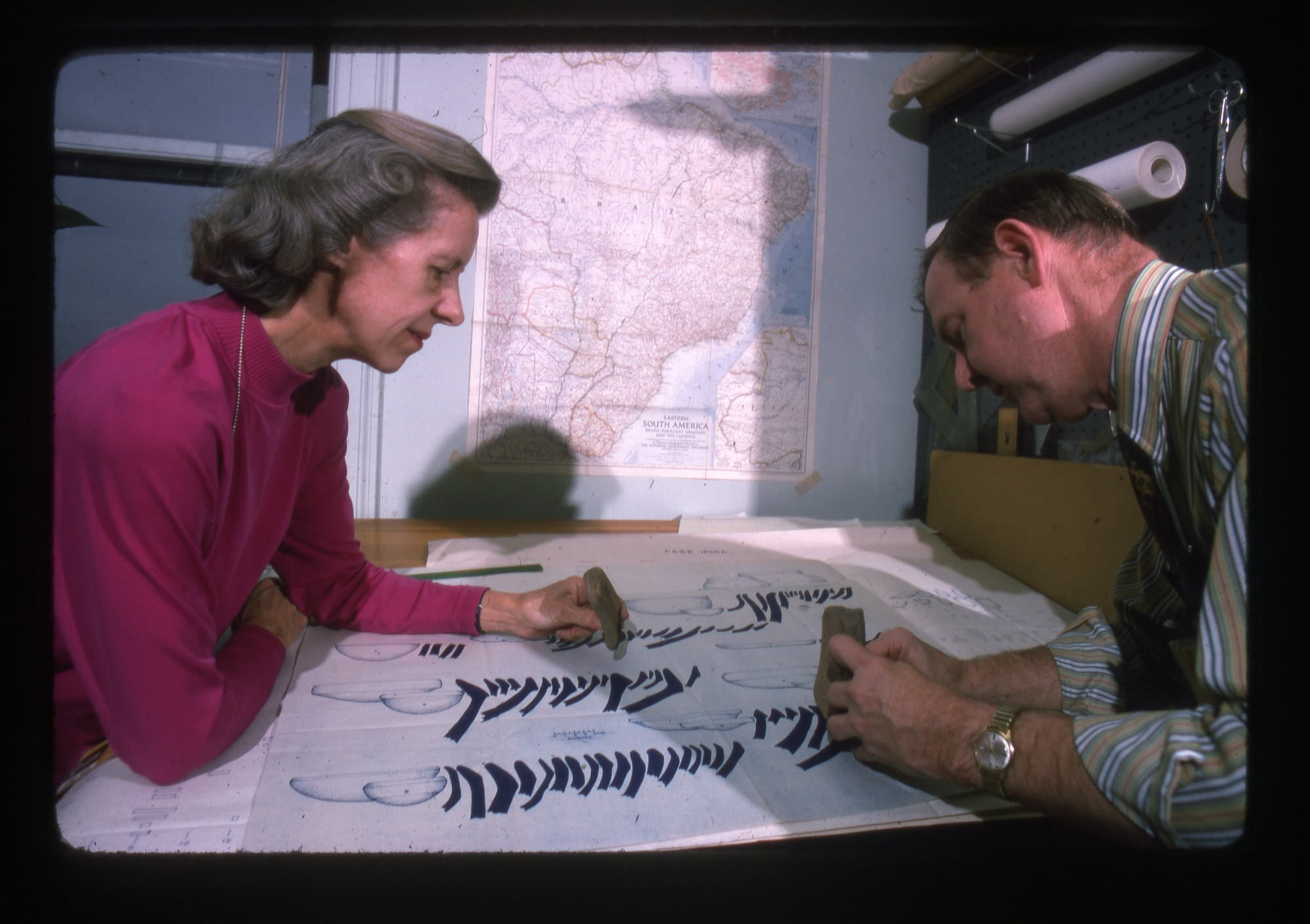 Clifford Evans and Betty Meggers Leaning Over Diagram