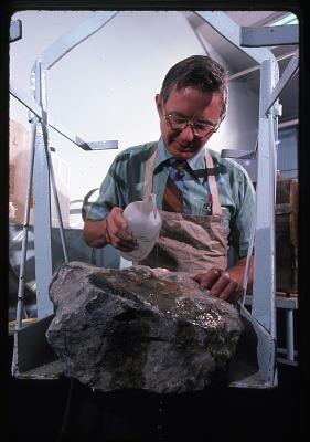 Dr. Richard E. Grant Examines Fossil in Matrix