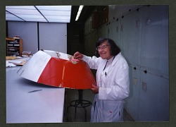 Roxie Laybourne Examining a Dented Aircraft Nose Cone