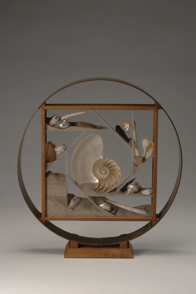 Wooden sculpture with shells and sand in the middle of a square frame housed in a circle frame.