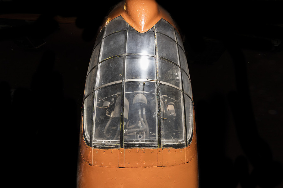 Top view of cockpit of an airplane. The airplane is painted orange and the cockpit window is closed.
