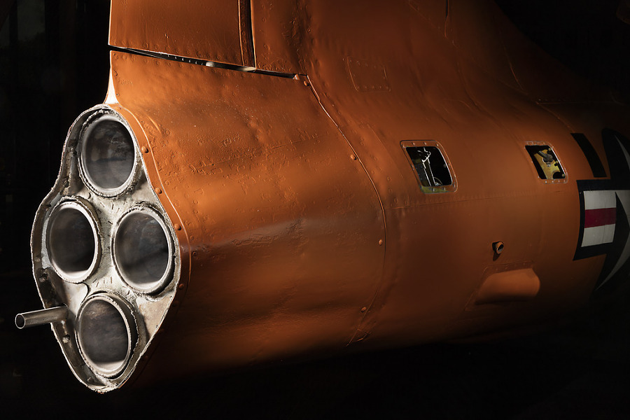 Side view of engine of an aircraft with three exhaust valves. The aircraft is painted orange.