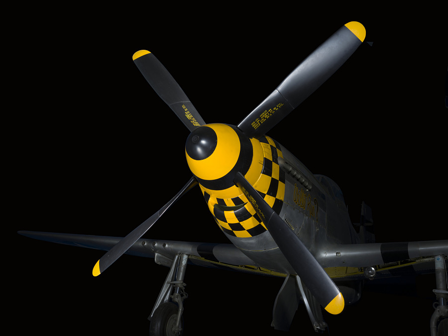 Four-blade propellers on nose of gray and yellow checkered P-51 Mustang aircraft