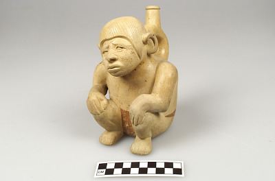 Stirrup-spout bottle in the form of a squatting man