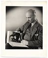 View Rockwell Kent reading <em>World Famous Paintings</em> digital asset number 0