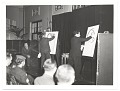 View Abril Lamarque watching two caricaturists on stage digital asset number 0