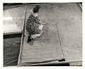 View Photograph of a woman working on a floor mural digital asset number 0