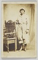 View Photographic postcard of a woman standing next to a wooden chair digital asset number 0