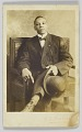 View Photographic postcard of a seated man holding a bowler hat digital asset number 0