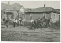 View Photograph of men running with a football in front of two houses digital asset number 0
