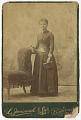 View Photograph of a woman standing next to a chair and holding a book digital asset number 0