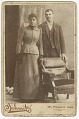 View Photograph of a couple standing behind a chair digital asset number 0