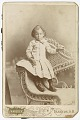 View Photograph of a toddler standing on a wicker chair digital asset number 0