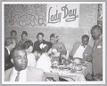 """View <I>Billie Holiday at a dinner party under a """"Lady Day"""" sign</I> digital asset number 0"""