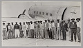 View Photographic print of migrant workers in front of a plane digital asset number 0
