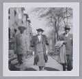 View Photo of a woman in fur standing between two men on the sidewalk digital asset number 0