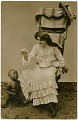 View [White woman in white dress holding food above crying African American child, photographic postcard] digital asset: [White woman in white dress holding food above crying African American child, photographic postcard].