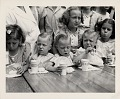 View [Children eating donuts and milk]: [black-and-white photoprint] digital asset: [Children eating donuts and milk]: [black-and-white photoprint]
