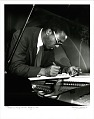 View Thelonious Monk [making notes at the piano]. [Photoprint, black-and-white digital asset: Thelonious Monk [making notes at the piano]. [Photoprint, black-and-white, undated.]