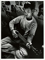 View Photographic History Collection: Carl Mydans digital asset: Young Japanese man strumming a guitar, Tule Lake Segregation Center, California