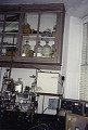 View Amino Acid Analyzer digital asset: Amino acid analyzer installed at the lab bench at Rockefeller University, 1996; note the carboys in upper cupboard used to maintain high nitrogen atmosphere for the ninhydrin solution