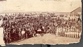 View Dakota Indians with Whites At Census Taking; Chief Gall in Center at Tables with Non-Native Men; Wood Frame and Log Buildings in Background n.d digital asset number 0