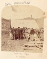 View Four Expedition Members and Women Outside Tent; American Flag Raised in Tent; Horse Trapping Hanging from Post; Powell Expedition 1871 digital asset number 0