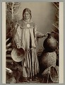 View Portrait of Young Woman in Native Dress with Blanket, Pitch- Covered Basket Jug, and Baskets 1888 digital asset number 0