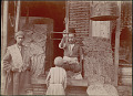 View Man, Breadmaker, and Three Boys in Costume Outside Brick And Wood Shop with Scales and Flatbreads; Bird in Cage Nearby 1890 digital asset number 1