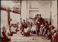 View Male Teacher and Schoolboys in Costume, Some with Pens and Paper, Around Boy with Feet Tied to Pole Held by Two Other, Demonstrating Bastinado (Punishment Involving Whipping of Bottoms of Feet) Inside Open Porch Classroom; Veiled Woman Nearby 1890 digital asset number 1