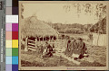 View Group of Women and Children in Costume Near Post and Woven Fence; Round Houses with Thatch Roofs Nearby n.d digital asset number 1