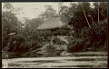 View View from Across River of Choco Platform House with Thatch Roof, Clothes on Railing; Dugout Canoe with Motor in River 1923 digital asset number 1