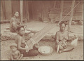 View Three Women in Costume, Cleaning Cotton in Basket, Spinning Cotton on Spindle, and Weaving Cotton on Backstrap Loom, Outside Plank House; Child Nearby 1902 digital asset number 1