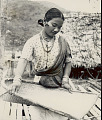 View Woman in Assamese-Indian Style Costume, Winnowing Grain? In Basket Near Pole and Thatch House 1954 digital asset number 1