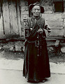 View Old Man in Costume with Rosary and Prayer Wheel Outside Plank House 1954 digital asset number 0