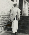 View Old Man in Costume Near Steps of Masonry and Wood Building 1954 digital asset number 0
