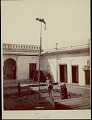 View Indian acrobat balancing on pole with man playing drum below him in courtyard, undated digital asset number 0