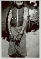 View Woman in Costume, Displaying Arm and Wrist Bracelets and Finger Rings, Outside Pole And Mud House; Clay? Chicken Nest Hanging from Roof 1965 digital asset number 1