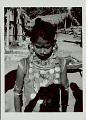 View Girl in Costume and with Ornaments Near Pole and Plank Houses with Thatch Roofs 1965 digital asset number 1