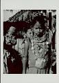 View Girl in Costume and with Ornaments Outside Plank House With Thatch Roof; Group Nearby 1965 digital asset number 0