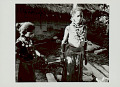View Two Girls in Costume and with Ornaments Outside Pole and Mud House with Holes (for Ventilation?) and Thatch Roof; Clay Jars Nearby 1965 digital asset number 0