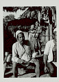 View Two Men, Woman, and Infant in Costume Outside Plank House With Thatch Roof 1965 digital asset number 1