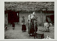 View Woman with Infant and Two Young Girls in Costume and With Ornaments Outside Pole And Mud House with Holes (For Ventilation?) and Thatch Roof; Calf, Chicken, and Dog Nearby 1965 digital asset number 1