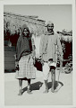 View Woman with Ornaments and Pipe, and with Man in Costume Outside Pole and Mud House with Thatch Roof 1965 digital asset number 1