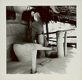 View Wood Trip-Hammer Pestle Used for Rice-Hulling on Porch of Pole and Mud House with Thatch Roof; Large Clay? Container For Storing Rice; Baskets Hanging on Wall 1965 digital asset number 0