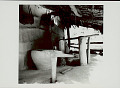 View Wood Trip-Hammer Pestle Used for Rice-Hulling on Porch of Pole and Mud House with Thatch Roof; Large Clay? Container For Storing Rice Nearby; Baskets Hanging on Wall 1965 digital asset number 0