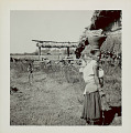 View Woman in Costume and with Ornaments, Carrying Basket on Head And Infant on Back Outside Pole and Mud House with Thatch Roof; Young Boy in Costume and Ping (Gallows-Like Wood Structure Decorated with Wheat for Fertility Feast) Nearby 1965 digital asset number 1